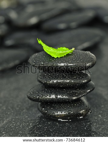 Black spa pebbles with rain drops on dark background