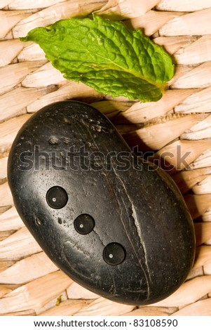 black spa stone with drops and a green leaf on wooden ground