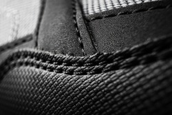 Black sport sneakers closeup. Seams and texture closeup. Detailed macro photo. The concept of comfortable casual shoes.