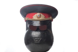 Black sports kettlebell similar to the head USSR policeman wearing a USSR Soviet Union police uniform cap and a black glasses on white background