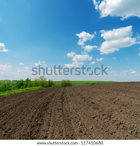 black spring field and cloudy sky