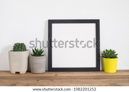 Black square frame poster with cactus on table in room. Houseplant and home decoration concept.