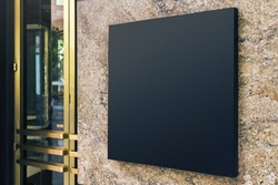 Black square signboard on the marble wall of a modern business center, mock up