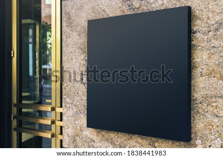 Black square signboard on the marble wall of a modern business center, mock up Stockfoto ©