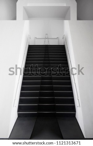 Black staircase in white wall. Abstract architecture / interior fragment in black and white. Architectural background in minimalism style.