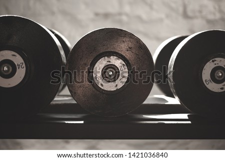 Black steel dumbbell set. Close up of dumbbells on rack in sport fitness center. Workout training and fitness gym concept.