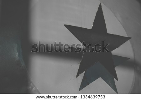 Black steel five-pointed star on a gray metallic background. Star Shadow