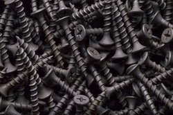 Black steel self-tapping screws used in handicrafts background texture