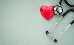 Black stethoscope, red heart with cardiogram for check-up on table background. Stethoscope equipment of doctor medical use to diagnose heartbeat. World heart day. health care and cardiology concept.