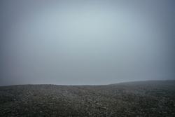 Black stone field in dense fog in highlands. Empty stone desert in thick fog. Zero visibility in mountains. Minimalist nature background. Dark atmospheric foggy mountain landscape. Foggy minimalism.