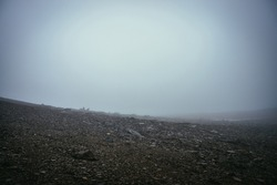 Black stone field in dense fog in highlands. Empty stone desert with sharp stones in thick fog. Zero visibility in mountains. Minimalist nature background. Dark atmospheric foggy mountain landscape.