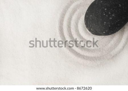 Black stone on raked white sand of a zen garden