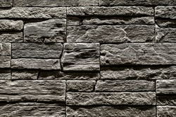 Black stone slate texture background, slate stone wall. decorative tiles for wall decoration. Black brick. loft decor style. structural surface imitating old brick. close-up of black stone wall