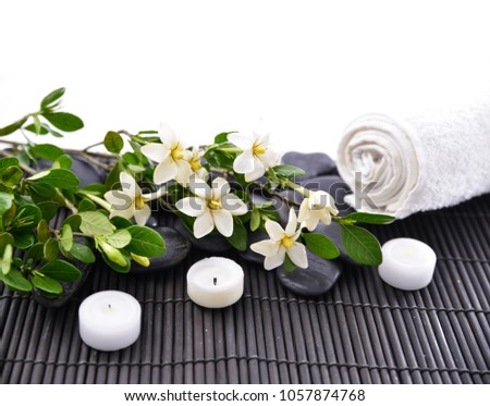 Black stones and candle ,pole of black stones and gardenia on mat