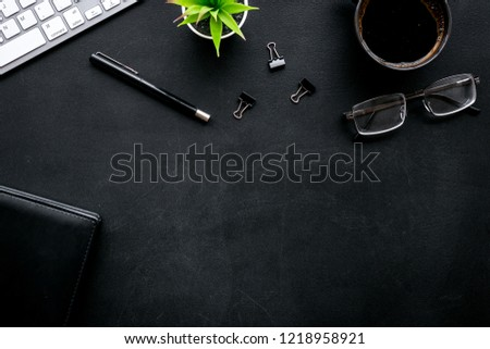 Black strict office desk, monochrome. Computer keyboard, expensive black notebook, glasses, coffee. Top view copy space #1218958921