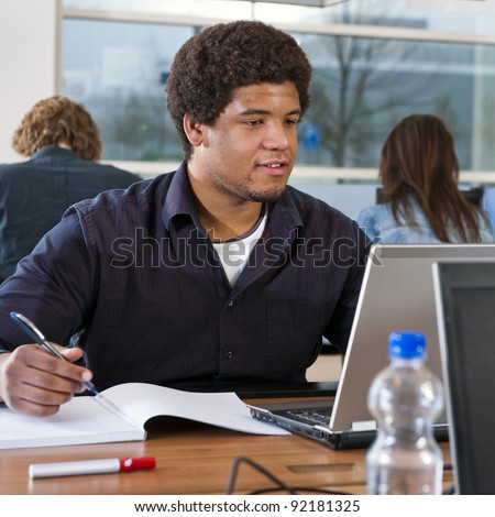 Black student working in a library, taking notes, and doing research online on his laptop, with two other students in the background