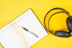 Black studio headphones and a diary on a yellow background, flat lay. Open blank notebook with pen