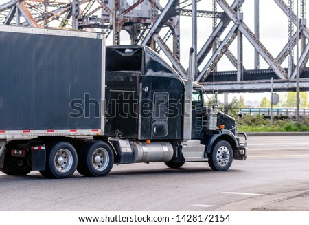 Black stylish big rig classic industrial semi truck with chrome accessories and vertical exhaust pipe transporting commercial cargo in covered black semi trailer moving on the road under the bridge #1428172154