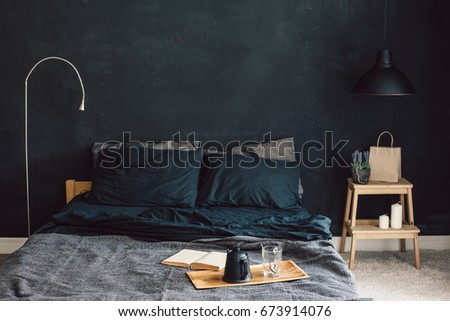 Black stylish loft bedroom. Unmade bed with breakfast and reading on tray. Lamp and interior decor over blank blackboard wall with copyspace. Cozy modern living space. #673914076