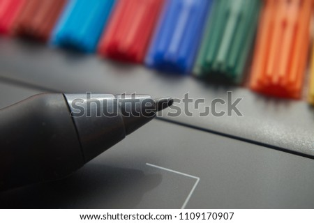 Black stylus pen on digital graphic tablet for illustrators and designers with colored markers in background. Macro view, free space and selective focus #1109170907