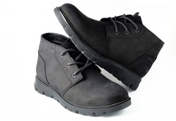Black suede chukka boots isolated on white.