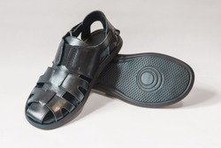 Black summer men's sandals on a light background. Comfortable sandals for hot weather for every day