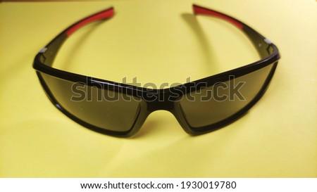 Black sun glasses closeup in yellow background Stok fotoğraf ©