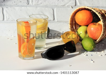 Black sunglasses next to orange and lemon juice, fruit in a basket. Morning refreshments on a hot summer holiday are good for dieting, black glasses for being on the beach #1401113087