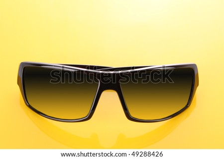 Black sunglasses on yellow  background