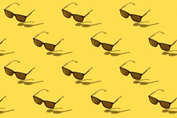 Black sunglasses on yellow background, copy space. Illuminating. Color of the year 2021. Top view, flat lay. Summer concept