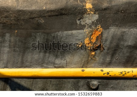 Black surface with a bright yellow stripe on the side of the boat. Fishing boat with damage. Black surface with bright details. Damaged black surface. Texture of damaged black surface.