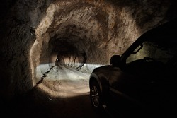 Black SUV car rides through a gloomy tunnel. Driving on the night dangerous road in the headlights.