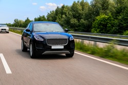 Black suv speeding on fast road. Jaguar E-Pace on a higway