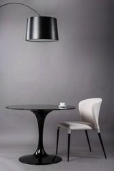 Black table, chair and the floor lamp on gray background. Modern furniture composition for interior.