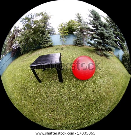 Black table, red ball on green grass with fish eye