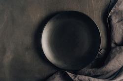 Black table setting: plates, napkin, silverware on black wooden background