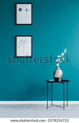 Black table with a silver, flower vase and posters on green wall in anteroom interior #1078256723