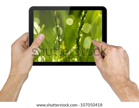 Black tablet pc with grass wallpaper in hands on white background. Portable computer