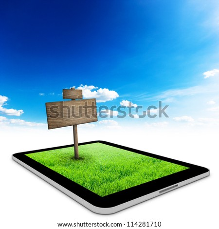 Black tablet with field and road sign on it.Business concept background