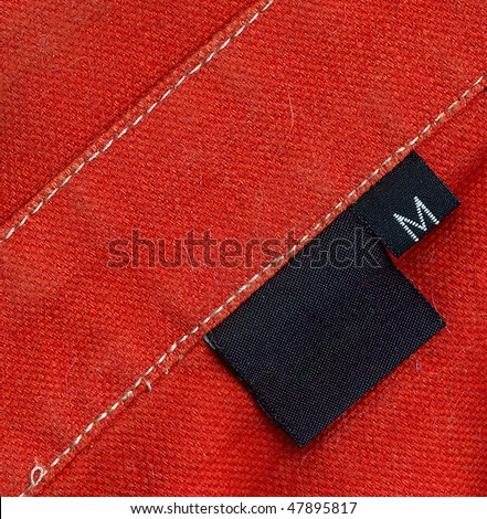 Black tag on a red denim textile