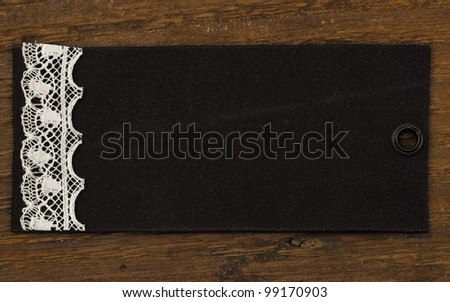 black tag with lace on the wooden background