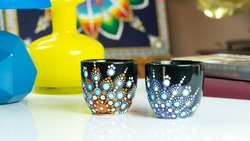 Black Tea Cups with dot mandala painting kept on a table with other props