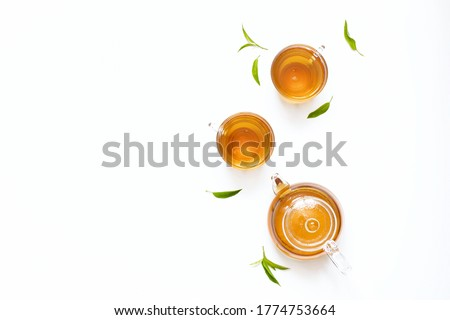 Black tea, green tea in a glass teapot with tea leaves. Top view