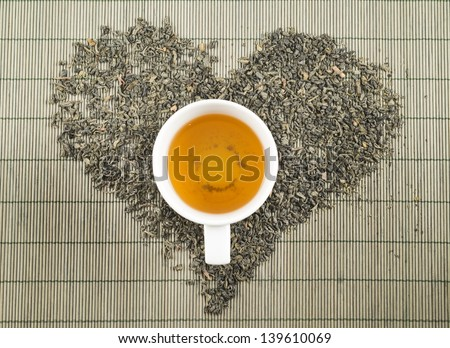 Black tea heart shape over bamboo mat top view with teacup