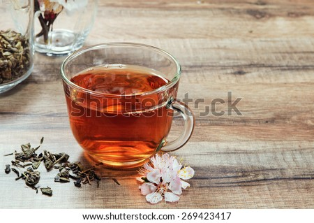 Black tea in a cup on a wooden table. Next to a cup of tea bouquet of blossoming apricot and scattered dry tea leaves