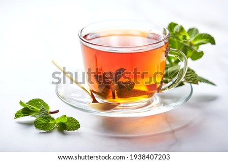 Black tea in glass transparent mug with mint leaves. Soothing tea, anti-stress. Foto stock ©