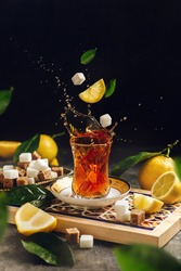 Black tea splash in armudu glass with lemons and sugar cubes