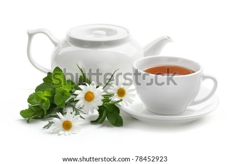 Black tea with fresh mint leaves and daisy. Isolated on white background.