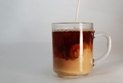Black tea with milk in a glass mug, on a gray background. A stream of cream pours into the mug. Hot, sweet Breakfast drink. At close range, up close.