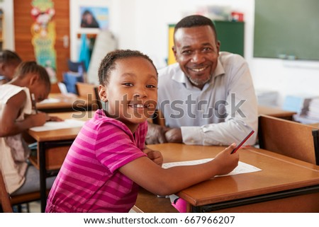 Black teacher and elementary school girl smiling to camera